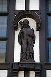 Statue William of Wykeham, Bishop of Winchester on exterior of Tudor building in Winchester High Street, England