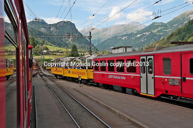 Swiss red Bernina Express trains stop at the Swiss town of Poschiavo in the Valposchiavo valley on the way to St. Moritz, Switzerland