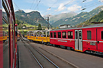 Swiss red Bernina Express trains stop at the Swiss town of Poschiavo in the Valposchiavo valley on the way to St. Moritz, Switzerland