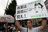A poster showing Shinzo Abe as Hitler at a protest against the revision of article 9 of the Japanese Constitution outside the Prime-Minister's house in Kasumigasaki, Tokyo, Japan. Monday June 30th 2014. Over 10,000 people showed their support for Japan's unique peace constitution and called on the government to halt its reinterpretation of Article 9 allowing Collect Self Defence which is expected to become law on July 1st