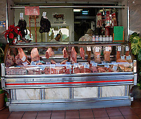 Butcher displaying cuts of meat in glass fronted display unit. Santa Cruz Market, Tenerife, Canary Islands,