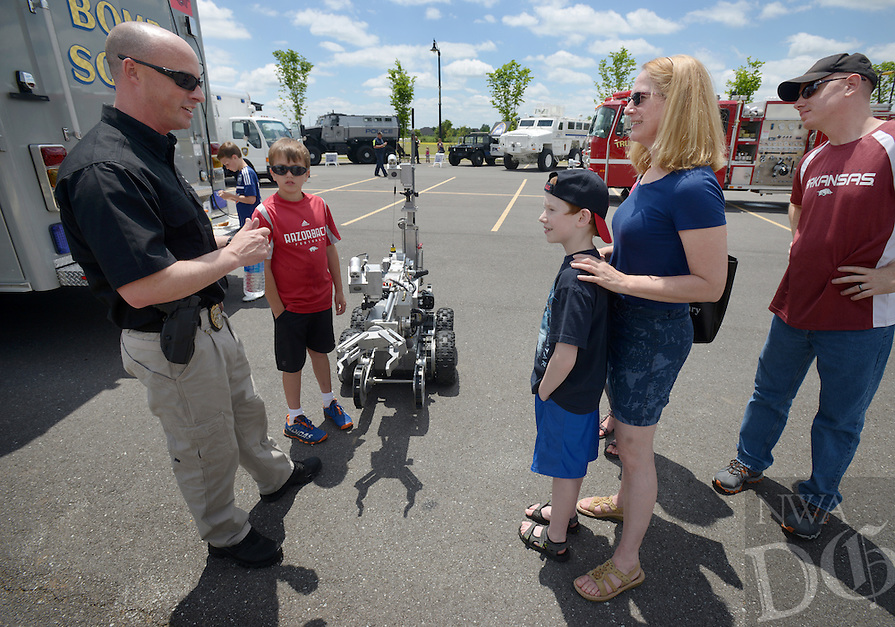 NWA Democrat-Gazette/BEN GOFF @NWABENGOFF<br /> Cpl. Josh Carlson talks about the Bentonville Bomb Squad's HYTAR robot on Saturday May 21, 2016 during a celebration of the Bentonville Police Department's 100th anniversary at the Bentonville Community Center. The event featured activities for children and displays of police and fire department equipment, including live demonstrations by the department's bomb squad and a vehicle extrication by the Bentonville Fire Department.