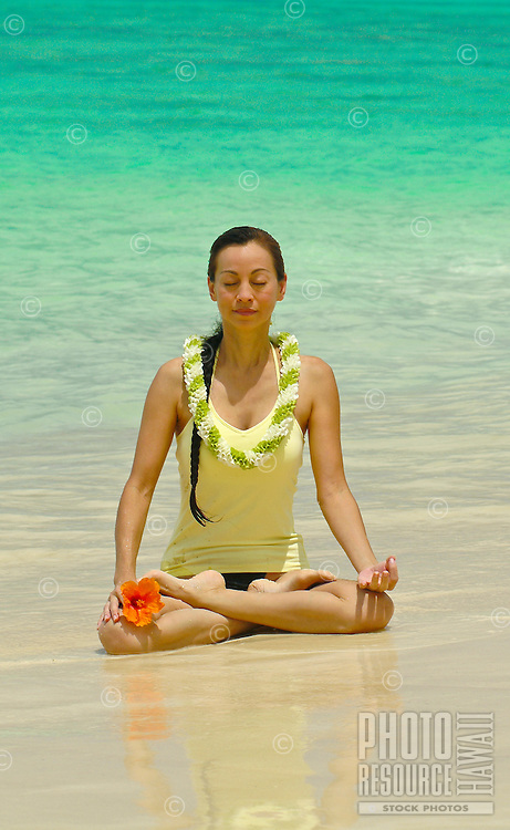 Woman meditating in lotus position wearing flower lei on white sand beach in Hawaii