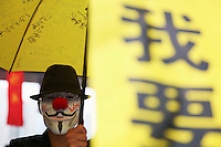 A pro-democracy protester wearing a Guy Fawkes mask holds a yellow umbrella and a banner, symbols of his movement in the part of Hong Kong's financial central district protesters are occupying November 2, 2014. The former British colony of Hong Kong, which returned to Chinese rule in 1997, has witnessed a month of protests calling on the Beijing-backed government to keep its promise of introducing universal suffrage. The protests have for the most part been peaceful, with occasional clashes between the student-led protesters and Beijing supporters seeking to move them from the streets.   REUTERS/Damir Sagolj (CHINA)