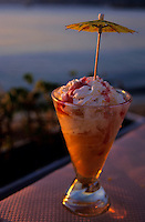 Peach ice cream sundae served with a cocktail umbrella in a glass.
