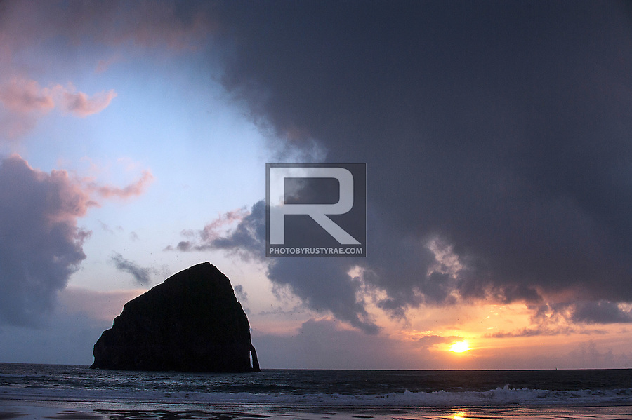 Clouds frame Haystack Rock at the beach at Pacific City, OR as the sun sets.