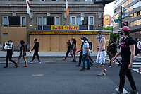 Demonstrators walk by a business that is boarded up to protect from vandalism during a protest in Washington, D.C., U.S., on Monday, June 1, 2020, following the death of an unarmed black man at the hands of Minnesota police on May 25, 2020.  More than 200 active duty military police were deployed to Washington D.C. following three days of protests.  Credit: Stefani Reynolds / CNP/AdMedia