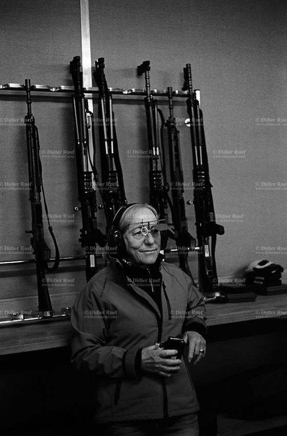 "Switzerland. Canton Glarus. Elm. Cantonal shooting fair. An elderly shooting woman stands near a rack holding  automatic or semi-automatic assault rifles SG 550. The SG 550 is an assault rifle manufactured by Swiss Arms AG (formerly Schweizerische Industrie Gesellschaft) of Neuhausen, Switzerland. ""SG"" is an abbreviation for Sturmgewehr, or ""assault rifle"". The rifle is based on the earlier 5.56mm SG 540 and is also known as the Fass 90 or Stgw 90. An assault rifle is a selective-fire rifle that uses an intermediate cartridge and a detachable magazine.19.08.2017 © 2017 Didier Ruef"