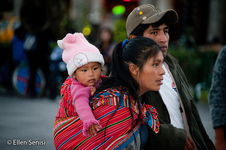Arequipa, Peru. Plaza de Armas (public square). Young family (Peruvian) consisting of father and mother (holding their baby girl in a baby carrier) look around the plaza. Mother is carrying the baby in a traditional Peruvian cloth wrap known as a K'eperina or Lliclla. No MR. ID: AL-peru.