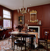 The Georgian dining room table has an Ikat runner by Robert Kime and is surrounded by antique French walnut chairs