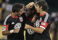 WASHINGTON, DC. - AUGUST 22, 2012:  Marcelo Saragosa (11) and Dejan Jakovic (5) of DC United with goal scorer Brandon McDonald (4) the Chicago Fire during an MLS match at RFK Stadium, in Washington DC,  on August 22. United won 4-2.