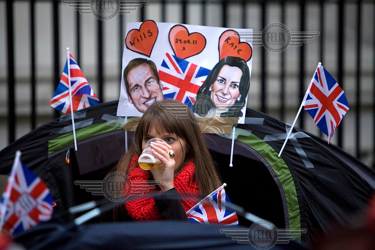 A woman drinks a beer as she prepares to camp overnight outside Westminster Abbey, London the day before the Royal Wedding between Britain's Prince William and Kate Middleton....