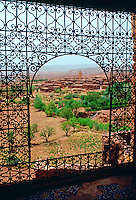 A view of Telouet through  an arched window decorated with ornamental filigree wrought iron work from Telouet Kasbah, Morocco.