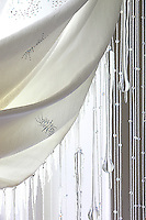 "A detail showing the snowflake embroidery on a white curtain and the icicle-like Swarovski crystal pendants hanging in the window of the ""Reine des Neiges"" bedroom"