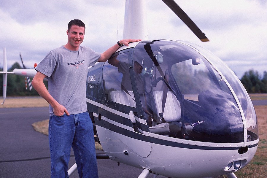 A male in his early twenties stands next to a Robinson R22 trainer helicopter.