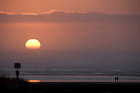 A couple wanders along the beach during sunset near Long Beach, Washington Saturday Feb. 7, 2009.