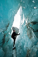 "Young woman in the ice cave or as glacier guides call it ""iris"" on Franz Josef Glacier - Westland National Park, West Coast, New Zealand"