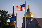 July 11, 2019; The Notre Dame and U.S. flags fly in front of the campus skyline (Photo by Matt Cashore/University of Notre Dame)