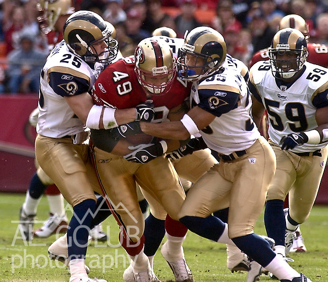 St. Louis Rams defensive backs Rich Coady (25) and Aeneas Williams (35) tackle San Francisco 49ers tight end Aaron Walker (49) on Sunday, November 2, 2003, in San Francisco, California. The 49ers defeated the Rams 30-10.