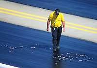Apr. 14, 2012; Concord, NC, USA: An NHRA official inspects the track after it started coming apart during qualifying for the Four Wide Nationals at zMax Dragway. Mandatory Credit: Mark J. Rebilas-