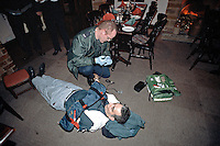 Paramedic ambulance crew attending to a casualty that fell over and broke (swan neck brake) his arm in a pub. The casualty had fainted. The paramedics are placing an air splint onto his arm. This image may only be used to portray the subject in a positive manner..©shoutpictures.com..john@shoutpictures.com