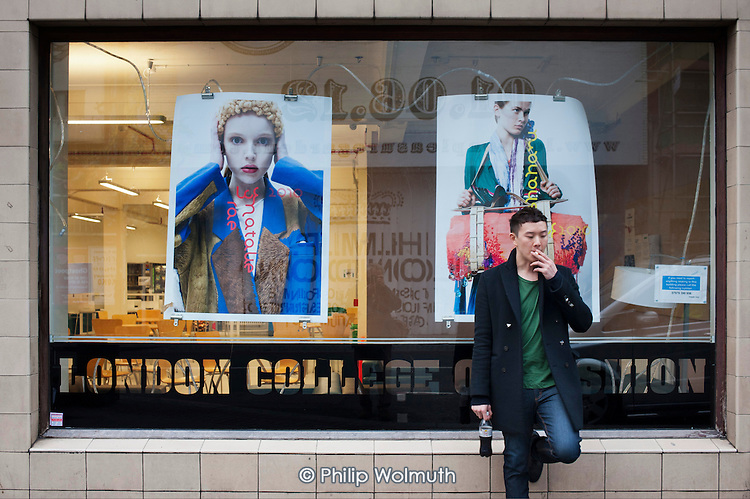 A student smokes outside the London College of Fashion, Shoreditch, London, a run-down commercial district  also known as Silicon Roundabout, which is undergoing gentrification as it becomes a centre for web-based companies and IT start-ups.