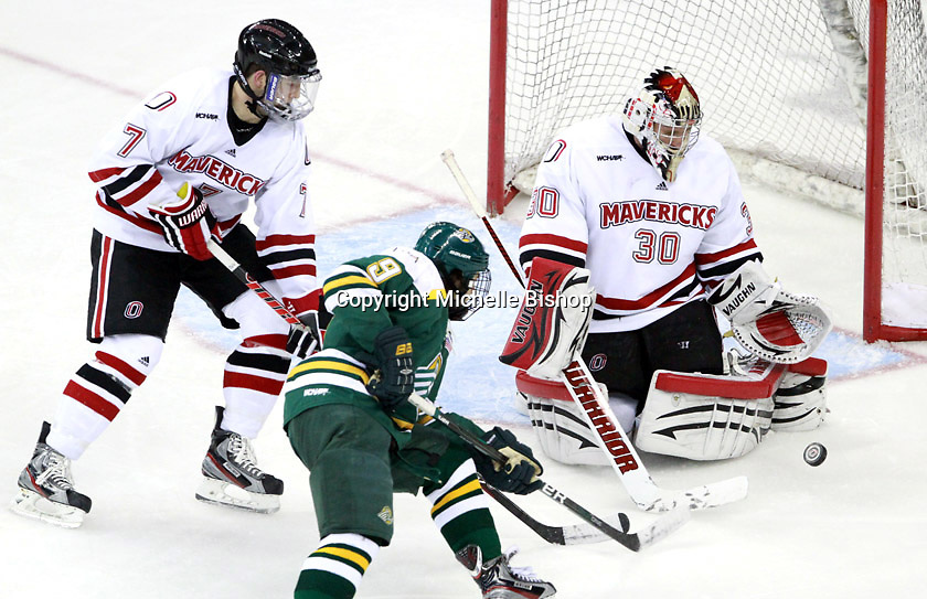Nebraska-Omaha goalie John Faulkner sets to stop a bouncing puck as Michael Young and Alaska-Anchorage's Mark Pustin look on. (Photo by Michelle Bishop) .
