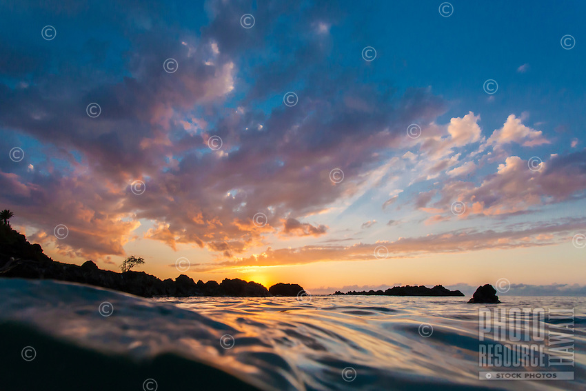 The colors of a vivid sunset reflect off the undulating waters of Waimea Bay, North Shore, O'ahu.