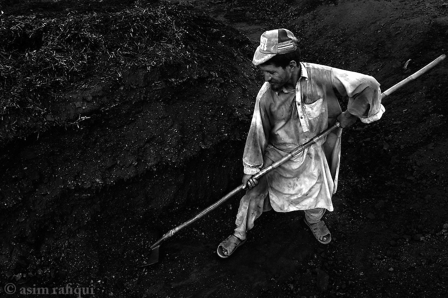 a man picks coal, bought to peshawar from as far away as chakwal in the punjab, to place into the fire pits where the bricks are baked.  jalozai, peshawar, pakistan.  september 2003&amp;#xA;&amp;#xA;copyright asim rafiqui 2003<br />