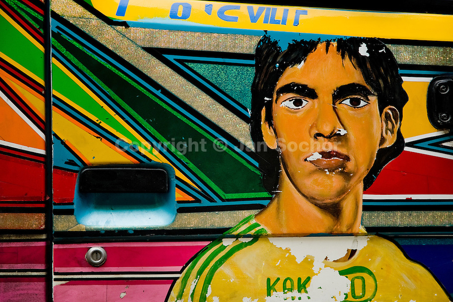 The Brazilian football player Kaká painted on the body of a tap-tap bus operating in Port-au-Prince, Haiti, 24 July 2008. Tap-tap vehicles serve as public transportation in Haiti. They are private, operate over fixed routes, departing only when full. Tap-taps are decorated with bright and shiny colors and with a lot of fancy designed elements. There are scenes from the Bible, Christian slogans, TV stars or famous football players often painted on a tap-tap body. Tap-tap name comes from sound of taps on the metal bus body signifying a passenger's request to be dropped off.