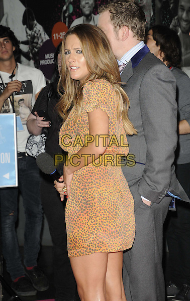 Caroline Flack.BT Digital Music Awards held at the Roundhouse, Chalk Farm, London, England..September 29th 2011.half length brown red orange dress leopard print looking over shoulder looks worried upset .CAP/CAN.©Can Nguyen/Capital Pictures.