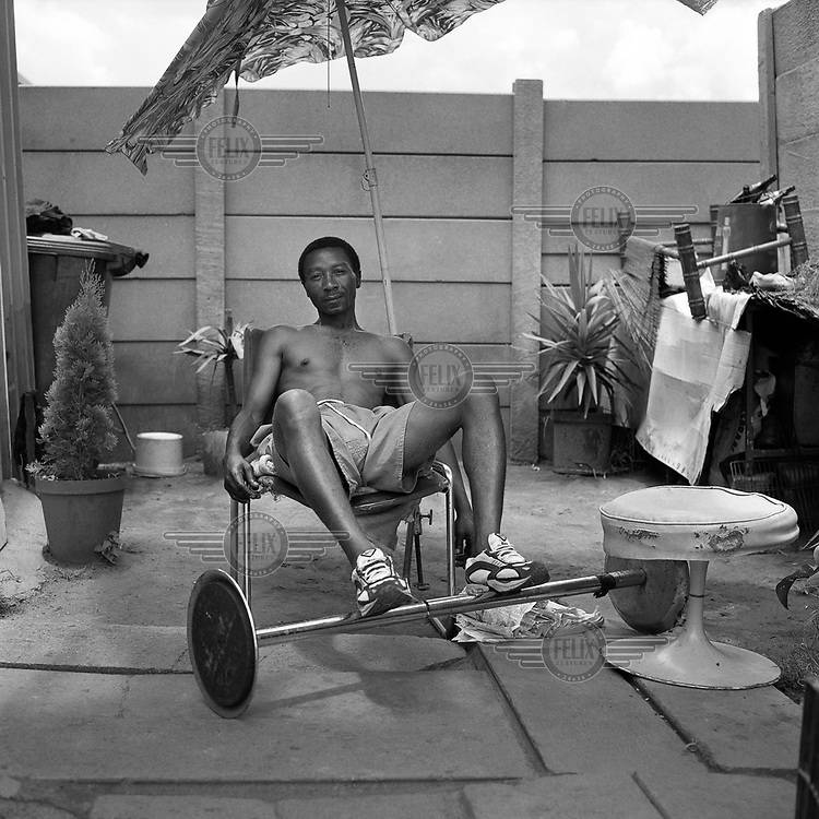 Davidson rests his feet on a set of exercise weights outside at the Top Star Drive Inn.