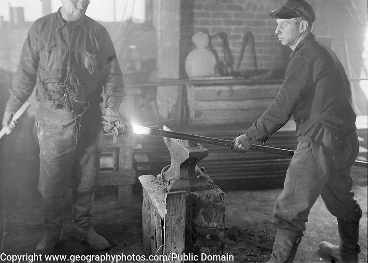 Two workers forging a metal rod in factory workshop, Finland 1950s- 1960s