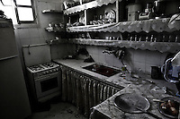 The kitchen items along with some vegetables are covered with a thin layer of dust from a house that received a mortar round in the Alakrat Heights - a region in rural Syria close to the city of Latakia.