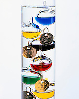 GALILEO THERMOMETER OR TERMOMETRO LENTOS. Principle of Galileo's Thermoscope. Specifically weighted floating bubbles predictably rise or sink in a liquid as the temperature of that liquid changes. The refraction of light by the liquid in the column causes the bubbles to appear different in size.
