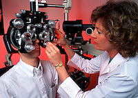 A female optometrist performs an eye exam on a male patient.