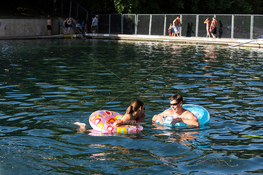 Attractive couple swimming at Barton Springs Pool, Austin's beloved spring-fed pool maintaining a 68ºF temperature year-round with lifeguards on duty.