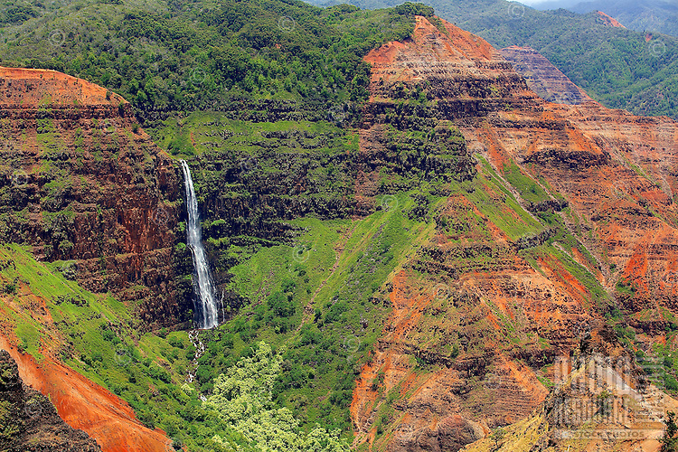 Waipo'o Falls flows freely into a lush green pocket amidst Waimea Canyon's red earth, Kaua'i.