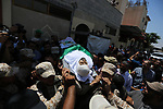 Mourners carry the body of Palestinian Abdul Karim Radwan, who was killed in an Israeli air strike, during his funeral in Rafah in the southern of Gaza Strip July 20, 2018. Photo by Ashraf Amra