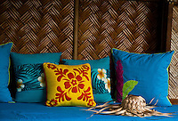 Floral print pillows on day bed with straw hat