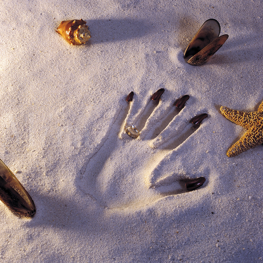 Concept image of a handprint in sand with a ring, fingernails and seashells.