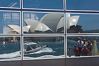 The Sydney Opera House, a passing boat and some camera happy tourists are reflected in the windows of the Ocean Terminal.