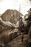 Sepia toned photo of young woman enjoying the scenic view of Dragontail Peak and Colchuck Lake, Alpine Lakes Wilderness, WA.