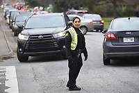 Melissa Steiner, patrolman first class with the Springdale Police Department, monitors traffic Friday, March 20, 2020, en route to pick up a box of free chicken t Springdale High School. Tyson Foods donated 55,000 pounds of chicken in 4,000 boxes as part of the school district's Spring Break Food Giveaway. Check out nwaonline.com/2003221aily/ and nwadg.com/photos for a photo gallery.<br /> (NWA Democrat-Gazette/David Gottschalk)