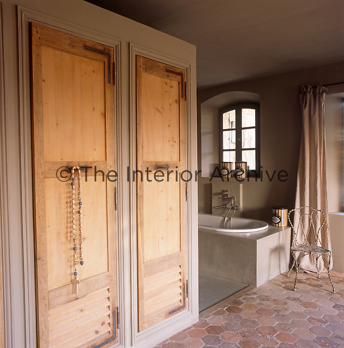 A grey bathroom with a bath set in a stone surround. A cupboard with a pair of wood louvre doors is set to one side.