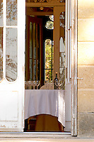 Door open to the garden with inside a table set with glasses and bottles for tasting wine, sunshine and shade, summer - Chateau Belgrave, Haut-Medoc, Grand Crus Classee 1855