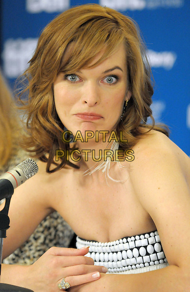 """MILLA JOVOVICH.""""The Stone"""" Press Conference - 2010 Toronto International Film Festival held at the Hyatt Regency, Toronto, Ontario, Canada, 10th September 2010..portrait headshot funny feather earrings dangly  strapless white beaded embellished .CAP/ADM/BPC.©Brent Perniac/AdMedia/Capital Pictures."""