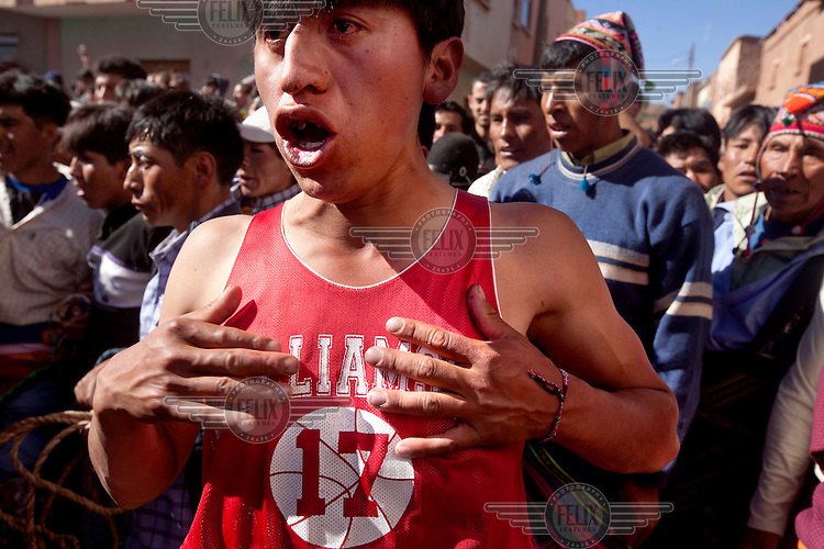A man in a baseball T shirt growls during the ritual fighting in the plaza of Macha. <br /> <br /> The people of Macha and surrounding communities carry on the pre-Columbian tradition of ritual fighting. The communities gather on the plaza of Macha to fight and dance in competition with each other. The blood that is spilled is an offering to Mother Earth. In return, the people ask for rain and a good harvest. This ritual is called tinku or fiesta de la cruz since the cross is also engaged in the festivities. The cross is dressed up, given offerings and brought from communities around Macha to the church in town. This syncretic festival melds pagan, pre-christian rituals with Catholic practice. /Felix Features