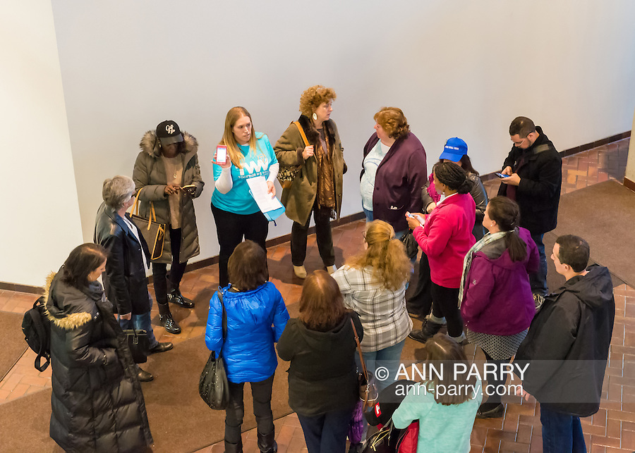 Melville, New York, USA. 24th January 2017. TWWLI admin (top center in blue shirt) SUE MOLLER, of Merrick, speaks with 14 members of Together We Will Long Island in lobby of bulding that U.S. Senator Chuck Schumer of New York has his Melville office in. They discussed plans before stopping by Schumer's office to share their concerns, especially about Trump's Cabinet appointees, #SwampCabinet. This Stop Trump Tuesday, #StopTrumpTuesday, event is part of nationwide political movement. Members of organizations such as MoveOn, Indivisible, and TWW plan to visit their Senators' offices each Tuesday duringTrump's first 100 days of presidency.