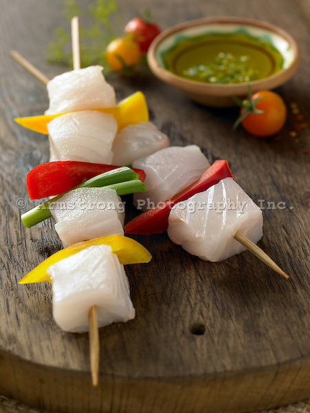 Chunks of raw halibut and bell peppers on a skewer